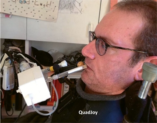 Ben writing using a mouth-controlled joystick called the QuadJoy. Photo courtesy of www.spinalcord.org
